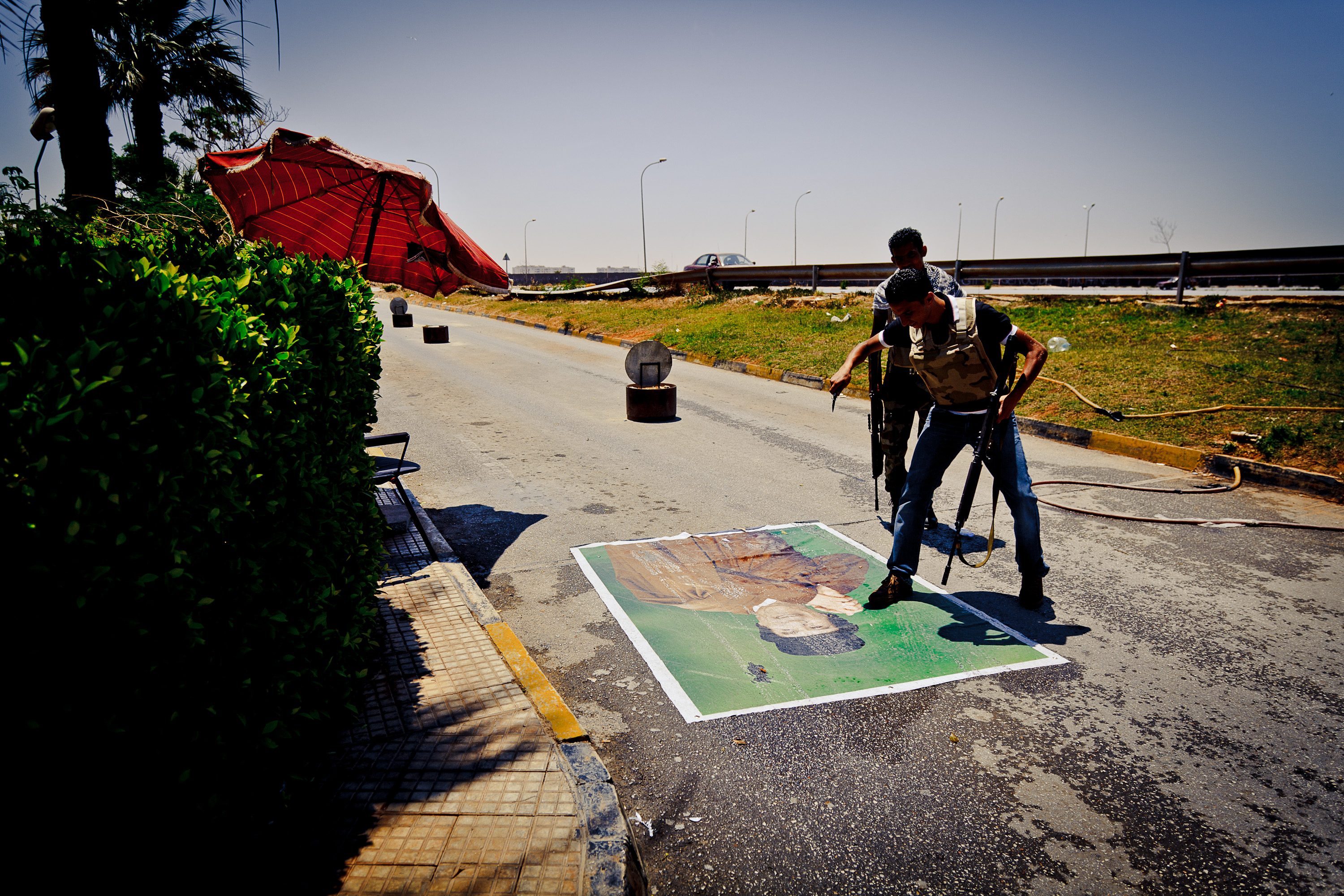An anti-ghadaffi rebel points a knife and steps on a poster of Ghadaffi in Benghazi, Libya.