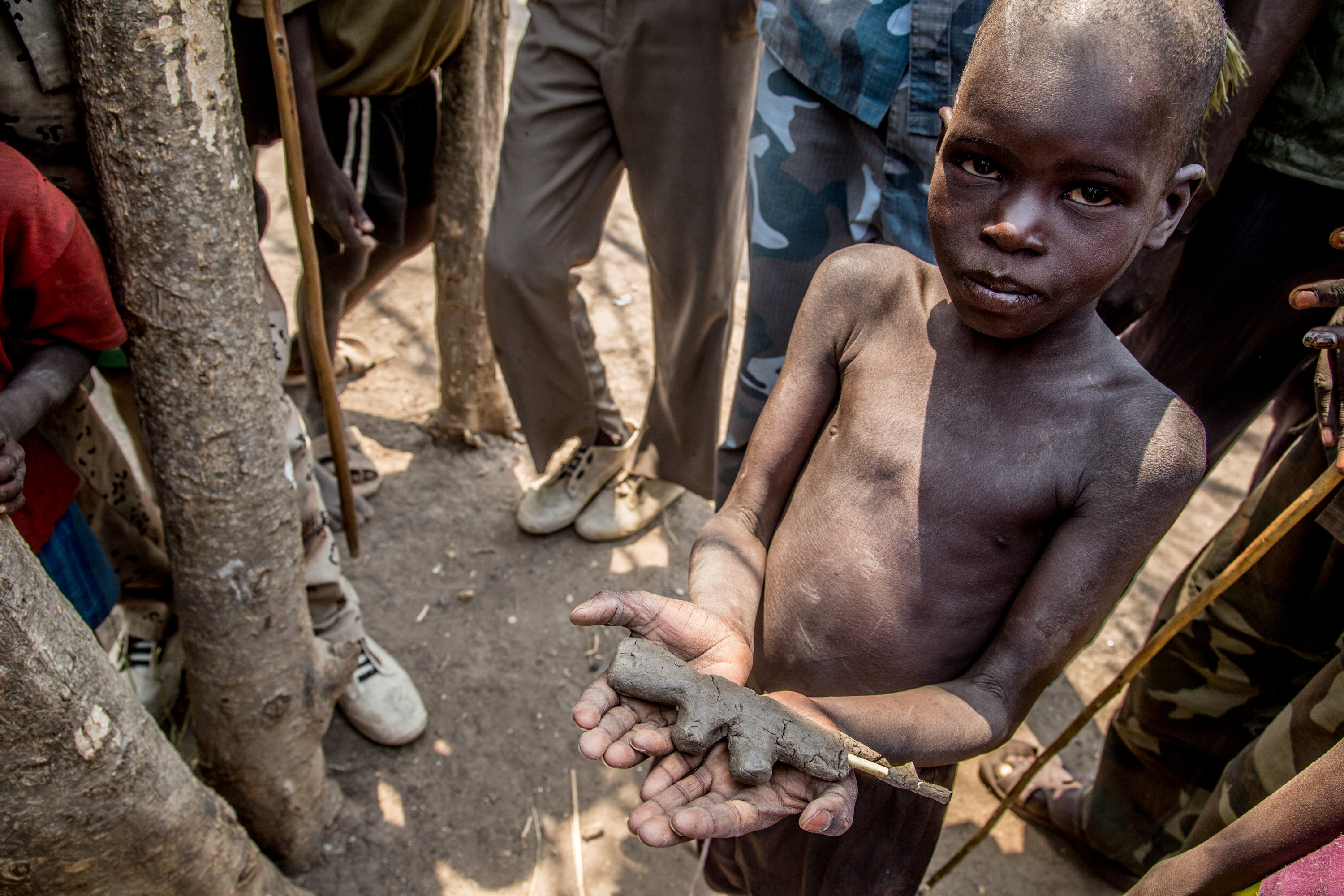 A boy displays a toy assault rifle made of mud and sticks at Dr. Riek Machar\'s secret base camp near Akobo, S Sudan.